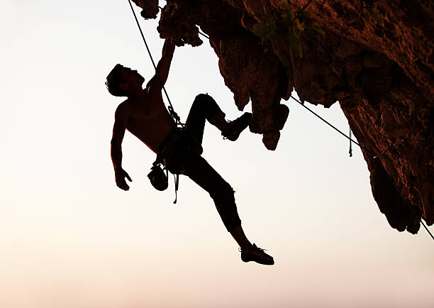 Silhouette of a rock climber hanging off cliff with one arm stock photo