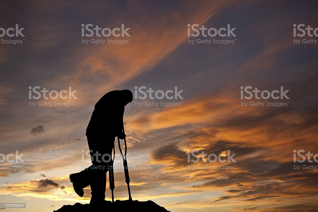 Silhouette of a Sad Injured Man With Crutches royalty-free stock photo
