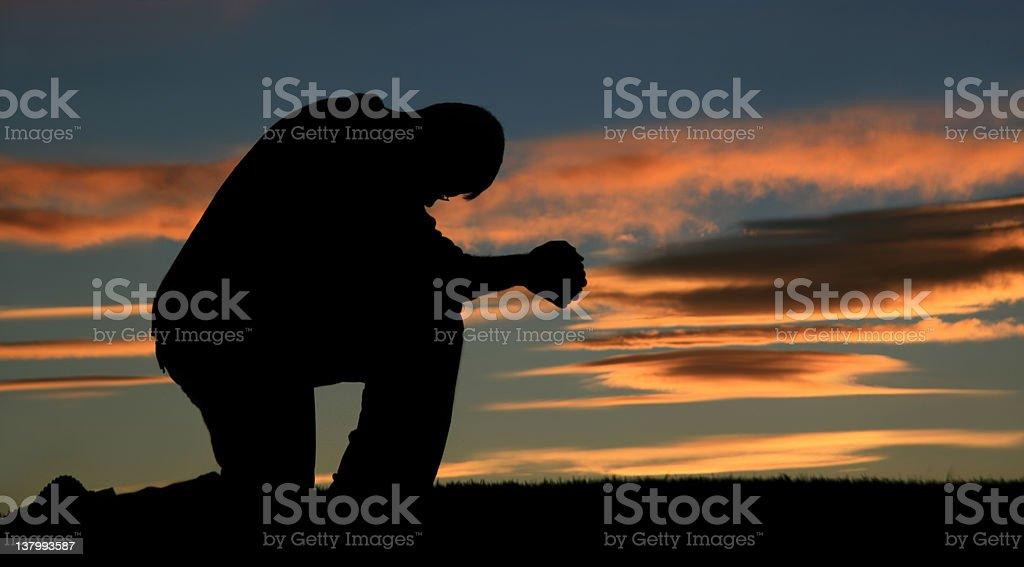 Silhouette of a Senior Caucasian Male Praying royalty-free stock photo