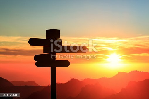 Silhouette of a sign with four directions with mountains and sunset in the background