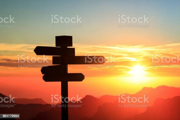 Photo of Silhouette of a signpost in a colorful sunset