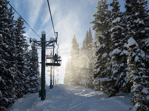 Silhouette of a skier and chair lift in blowing snow