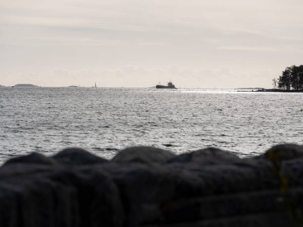 A silhouette of a small cargo vessel crossing the sunny horizon. stock photo