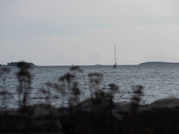 A silhouette of a small sailboat crossing the horizon on a sunny day. stock photo