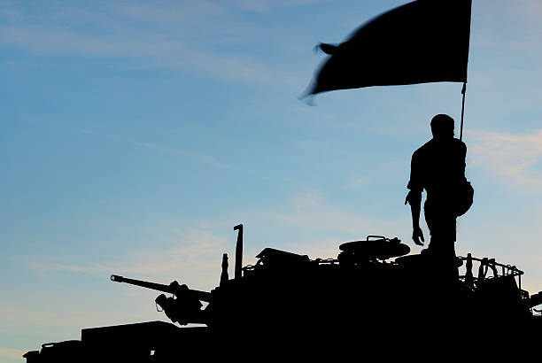 Silhouette of a soldier with a flag on a tank stock photo