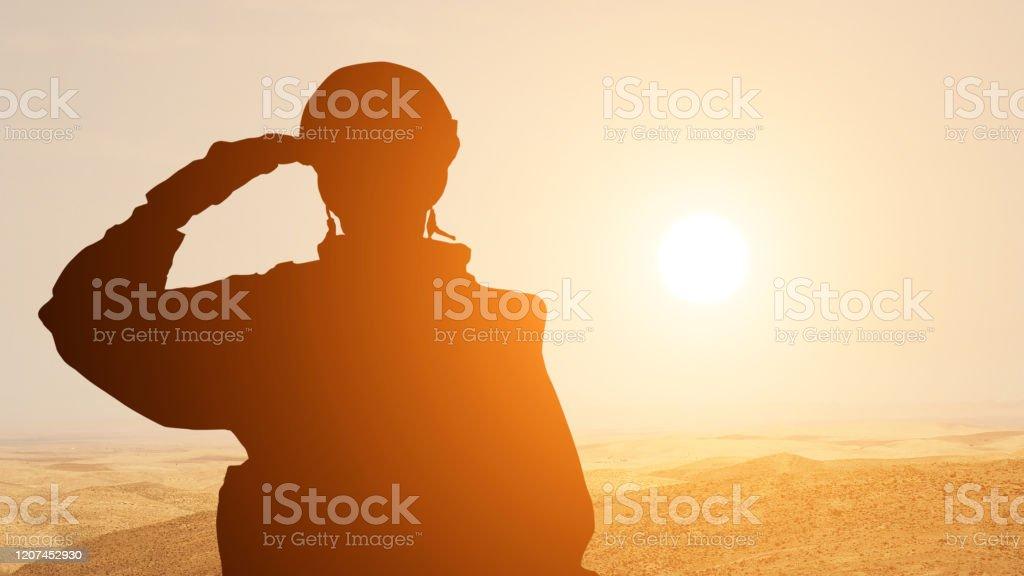 중동의 사막에서 일출에 대해 경례 하는 솔더의 실루엣. 개념 - 아랍 에미리트, 이스라엘, 이집트의 무장 세력 - 로열티 프리 Armed Forces Day 스톡 사진