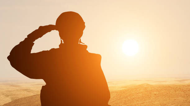 silhouette of a solider saluting against the sunrise in the desert of the middle east. concept - armed forces of uae, israel, egypt - tropa imagens e fotografias de stock
