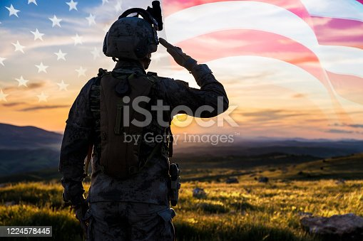 Silhouette Of A Solider Saluting Against US Flag at Sunrise