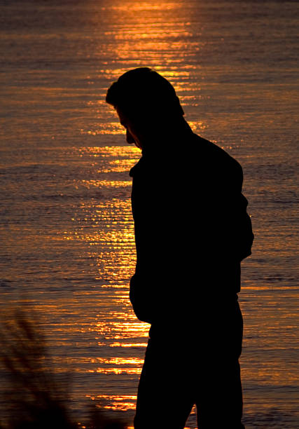 Silhouette of a solitary man by the sea at sunset stock photo
