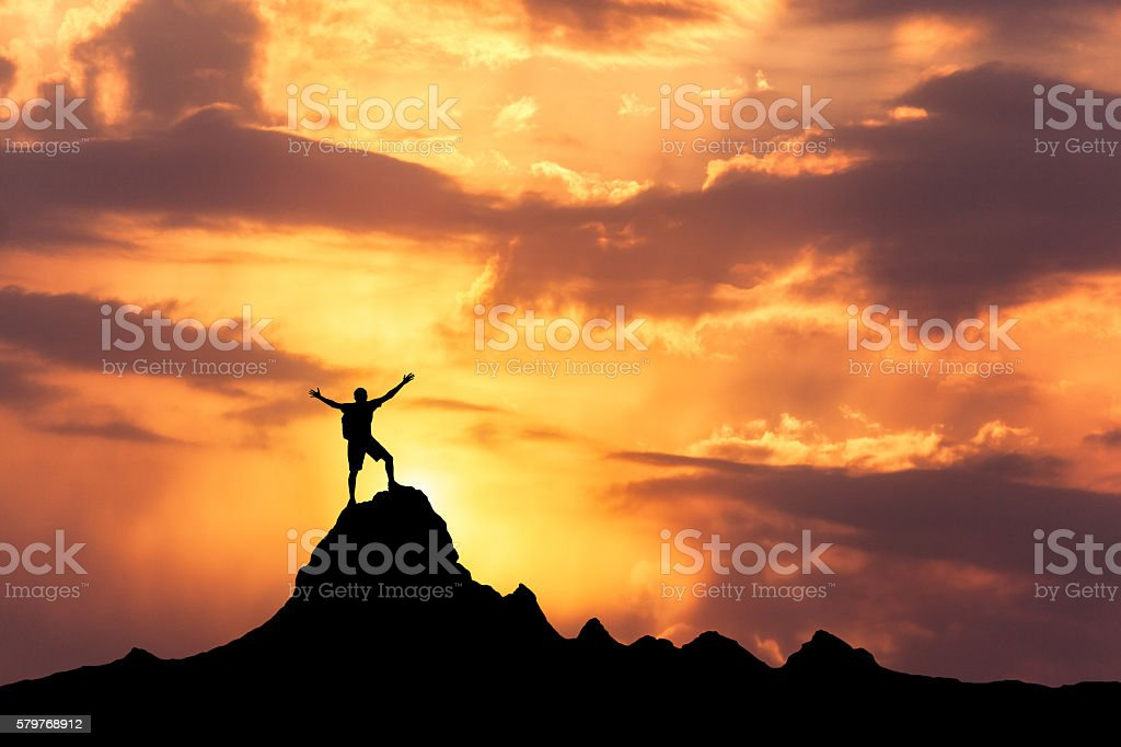 Silhouette of a standing happy man on the mountain peak stock photo