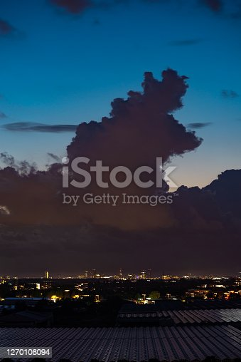Stormcloud near the city of `The Hague, Netherlands is silhouetted against the twilight sky.