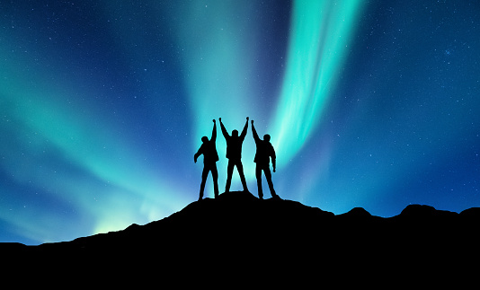 istock Silhouette of a team on the northen light backgroun. Concept and idea of active life 931477428