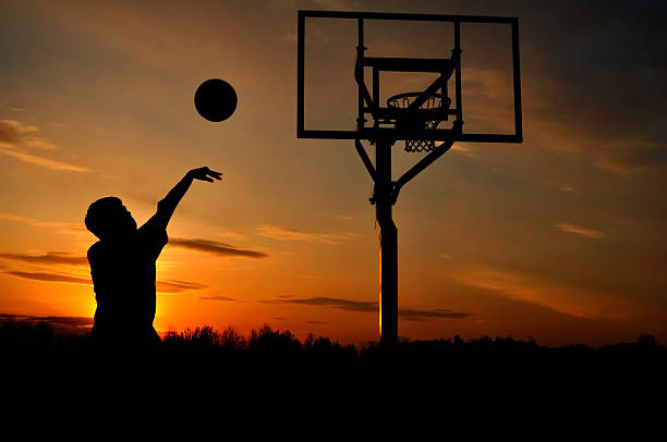 Silhouette of a teenage boy shooting a basketball at sunset Silhouette of Teen Boy Shooting a Basketball at Sunset, copy space jump shot stock pictures, royalty-free photos & images