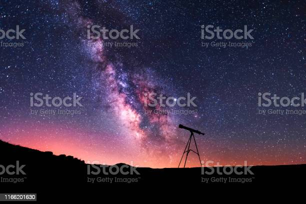 Photo of Silhouette of a telescope at the starry night and bright milky way galaxy.