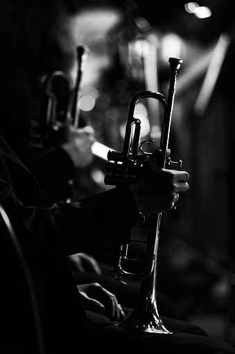 Silhouette of a trumpet in the hands of a musician in an orchestra in dark colors