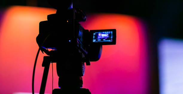 silhouette einer tv-kamera filmt eine live-übertragung - film oder fernsehvorführung stock-fotos und bilder