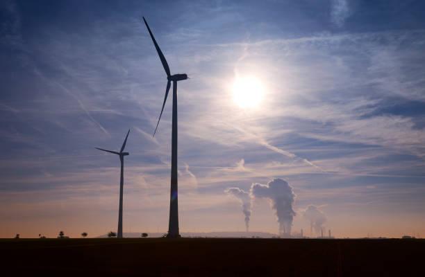 Silhouette von zwei Windenergieanlagen und Kohle befeuerten Kraftwerk – Foto