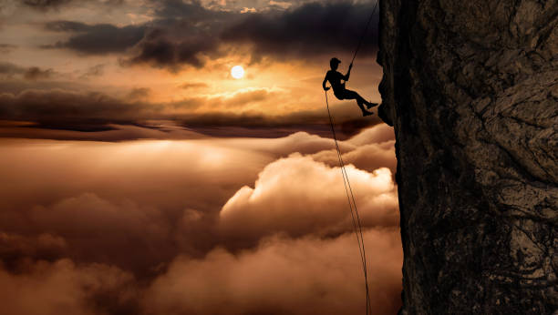 Silhouette of a Unrecognizable man rappelling down a steep cliff
