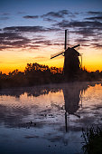 Silhouette of a windmill at the warm and red color sunrise in Hazerswoude-Dorp village, Netherlands