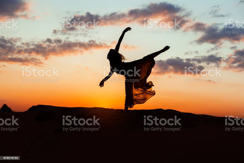 Silhouette of a woman at sunset. stock photo