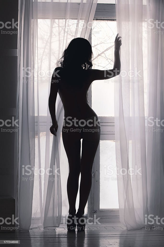 Silhouette of a woman  at the window stock photo