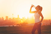 Silhouette of a woman drinking form a cold water bottle. She is exercising at sunset or sunrise. City of Sydney in the background. Copy space.