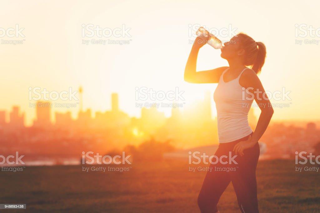 Silhouette einer Frau trinken bilden eine kalte Flasche Wasser. – Foto