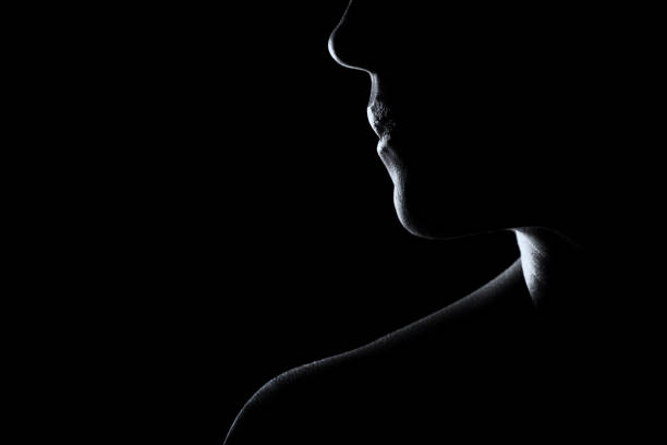 Silhouette of a woman face in black and white with rim lighting stock photo