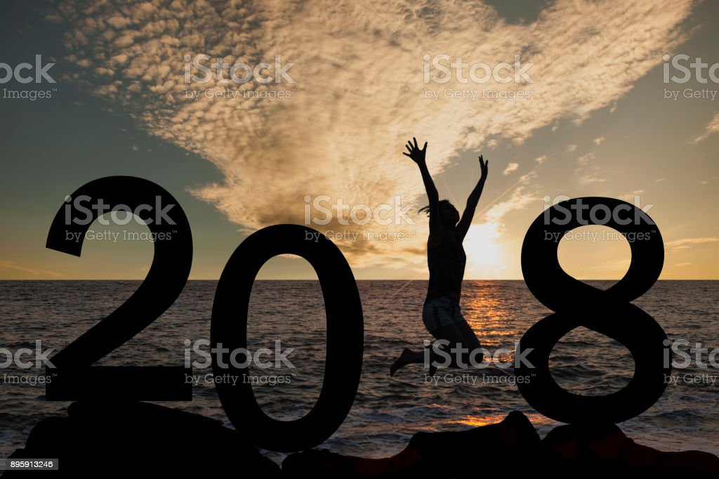 Silhouette of a woman jumping in 2018 on the hill at sunrise stock photo