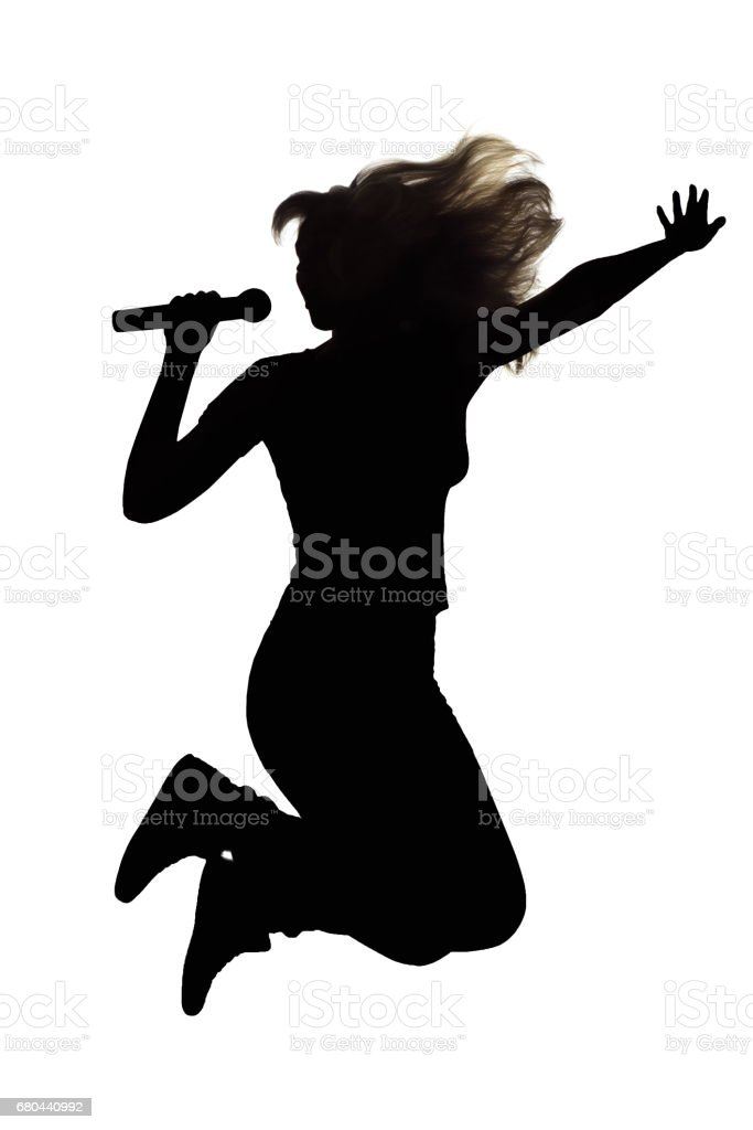 Silhouette of a woman jumping with a microphone up stock photo