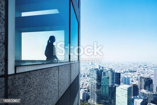 Woman's silhouette on a window in a skyscraper overlooking Tokyo, Japan.