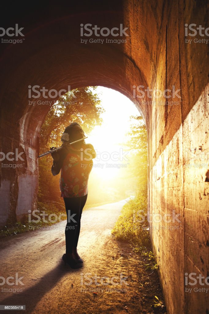 Silhouette Of A Woman playing Flute In Tunnel The silhouette of a beautiful African American woman playing her flute in a tunnel. 50-54 Years Stock Photo