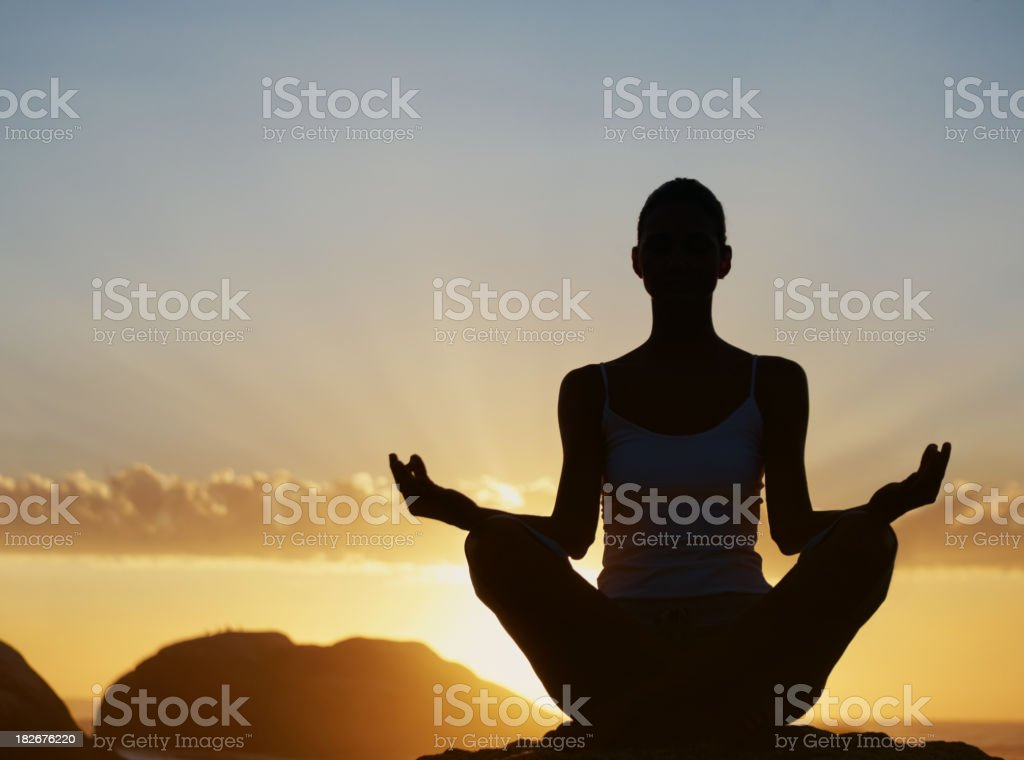 Silhouette of a woman practicing yoga at sunrise royalty-free stock photo