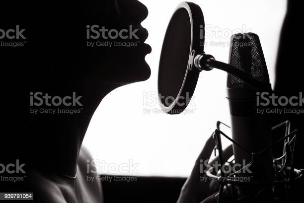 Silhouette of a woman singing a song in a recording studio. Black and White.
