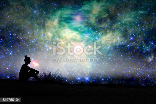 istock Silhouette of a woman sitting outside, starry night background 619750134