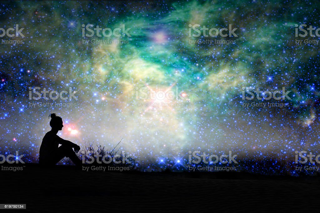 Silhouette of a woman sitting outside, starry night background stock photo