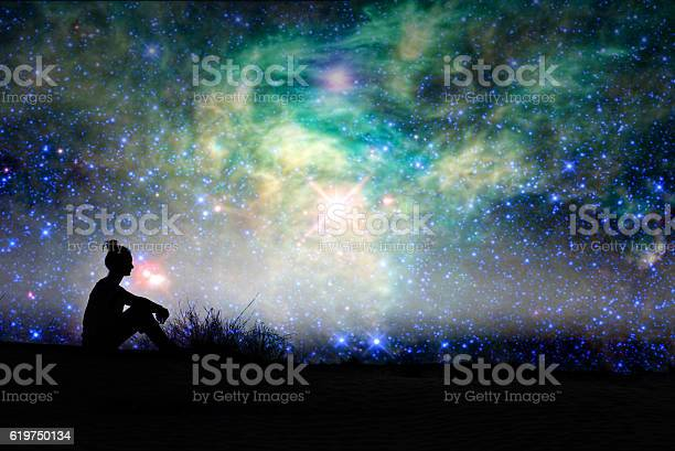 Photo of Silhouette of a woman sitting outside, starry night background