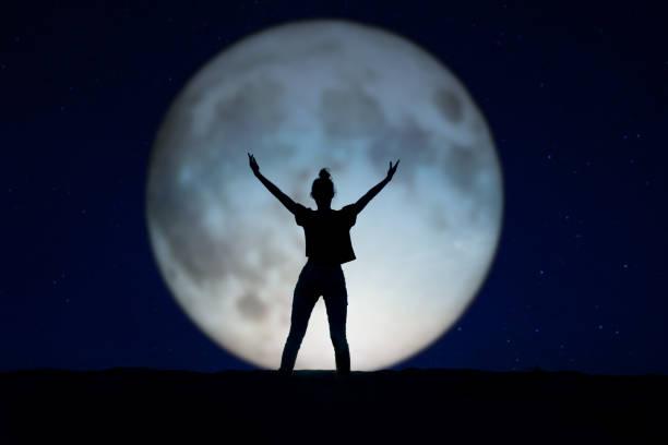 silhouette d'une femme debout dans la nuit avec les bras vers le haut, la lune géante dans le fond - pleine lune photos et images de collection
