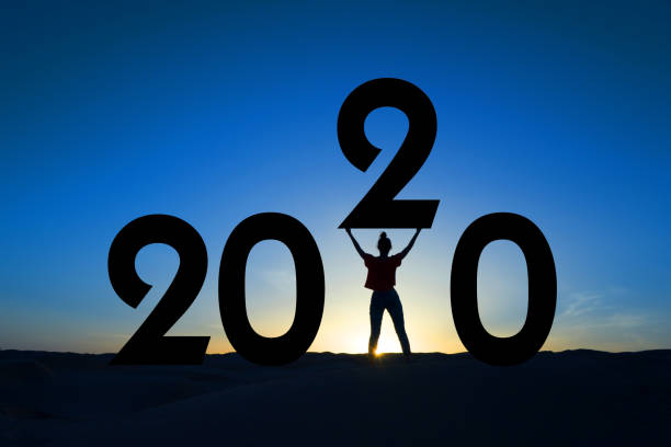 2020, silhouette of a woman standing in the sunrise, women empowerment, feminist new year holiday greeting card - политика и правительство стоковые фото и изображения