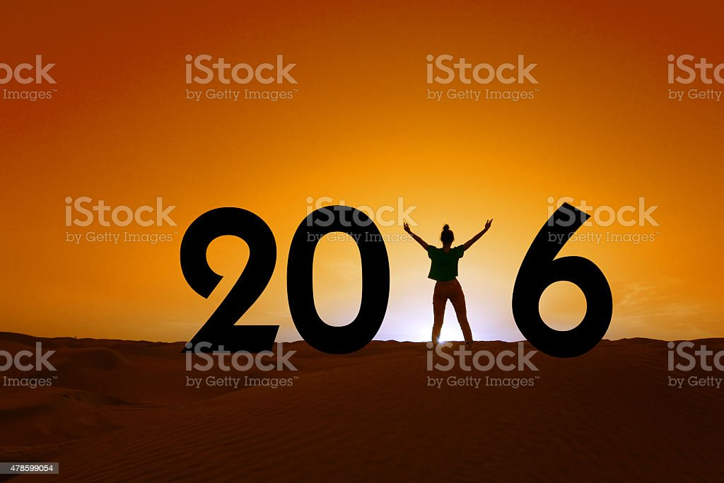2016, silhouette of a woman standing in the sunset stock photo