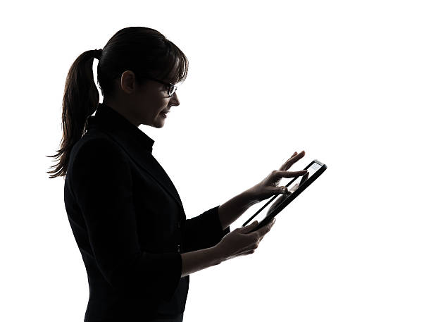 Silhouette of a woman using a table over a white background stock photo