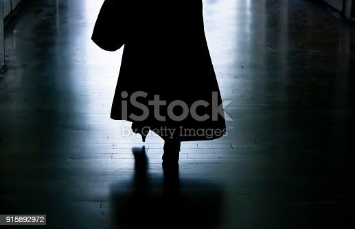 istock Silhouette of a woman walking away in dark alley 915892972