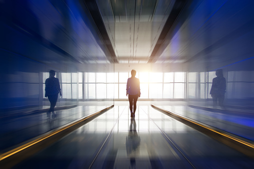 Silhouette of a woman walking into the light