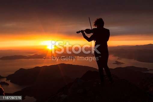 Silhouette of a woman with a violin at sunset on top of the mountain.