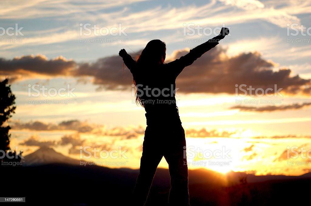 Silhouette of a woman with arms up outside during sunset royalty-free stock photo