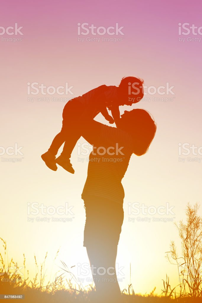 Silhouette of a woman with her child at sunset. stock photo