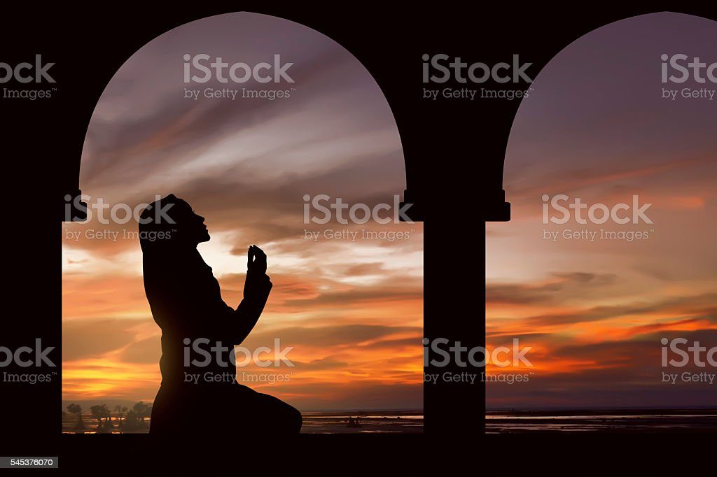 Silhouette of a women praying during sunset stock photo