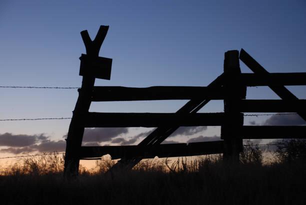 Silhouet van een houten hek tegen de koele en verwarmt kleuren van de ondergaande zon foto