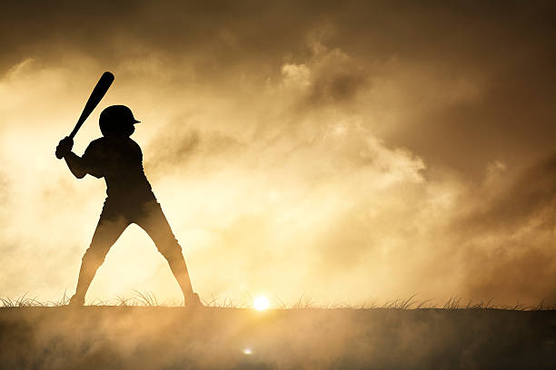silhouette of a young baseball player - softball stock photos and pictures