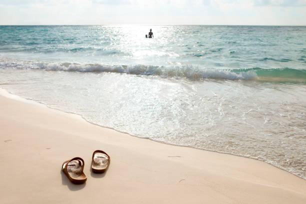 silhouette eines jungen paares spielen im meer am ende des tages - salzwasser sandalen stock-fotos und bilder